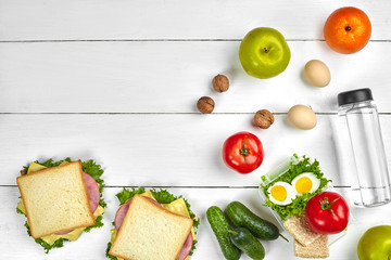 Lunch. Sandwich and fresh vegetables, bottle of water, nuts and fruits on white wooden background. Healthy eating concept. Top view with copy space