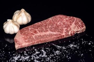 japanese Saga beef isolated on the black with salt and Garlic bulbs
