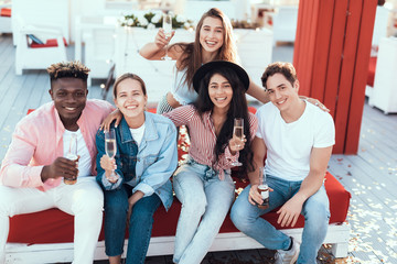 Portrait of beaming girls and cheerful males looking at camera while tasting glasses of champagne and bottles of beer. Glad lady wearing modern jacket. Positive friends during rest concept