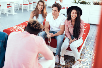 Positive male communicating with beaming ladies while sitting on cozy sofa outdoor
