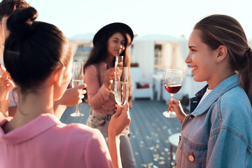 Optimistic ladies drinking alcohol liquid while talking together outside. They holding glasses in hands