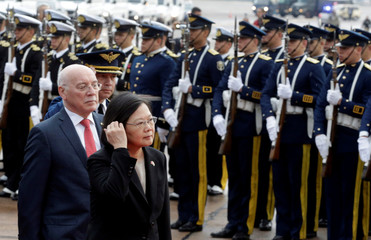 Taiwan's President Tsai Ing-wen walks past military guards alongside Paraguay's Foreign Minister Loizaga as she arrives for the August 15 swearing-in ceremony in Luque