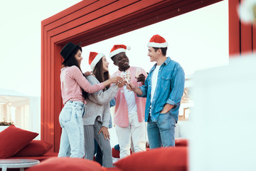 Happy males and smiling girls talking toast while tasting alcohol liquid. They wearing red hats during celebration of new year