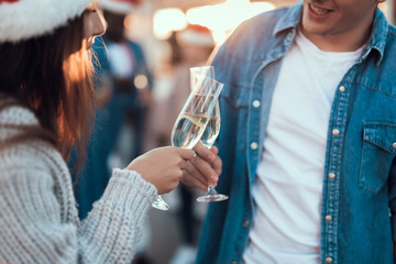 Positive guy clanging glasses of champagne with glad female during christmas celebration