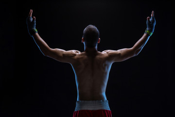 Rear view of strong young male boxer. Fitness male model wearing boxing gloves standing on black background.