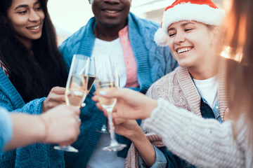 Optimistic ladies and cheerful men drinking glasses of delicious champagne while telling together. Happy friends celebrating new year concept