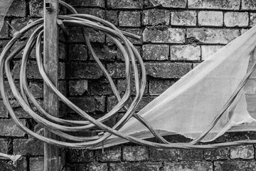 Black and white photo with a broken brick wall, wound wire and cloth