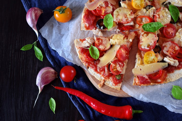 Pizza with cherry tomatoes, tomato sauce, cheese and basil leaves against the dark background. Mediterranean cuisine meal