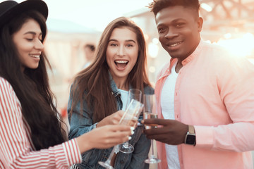Portrait of happy man and cheerful females enjoying glasses of champagne during party