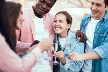 Smiling man embracing beaming lady while telling with happy friends. They drinking glasses of champagne during party