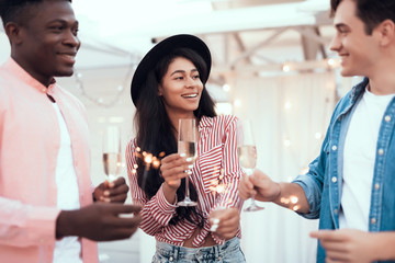 Cheerful woman speaking with cheerful friends while enjoying appetizing alcohol liquid