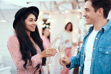 Beaming pretty lady talking with outgoing young man while tasting glass of delicious champagne