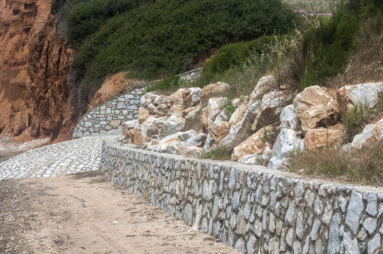 Reinforcing masonry stone wall on a slope of a beach seashore to prevent soil collapse