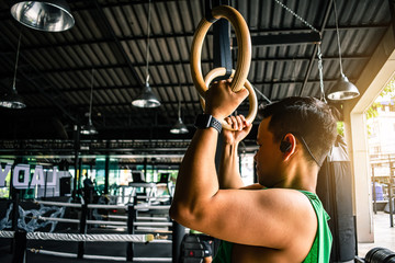 Asian man athlete gymnast rings exercise in gymnastics exercise chest