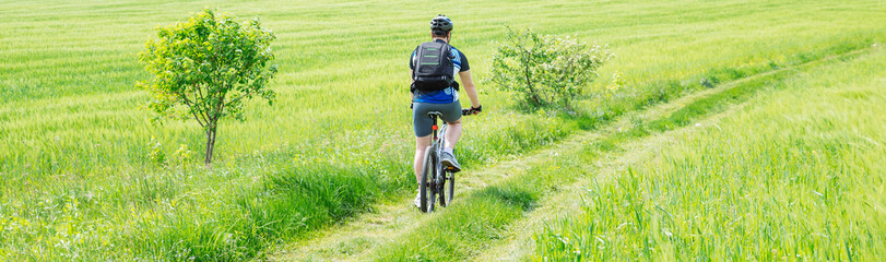 man riding bicycle by trail in green barley field. copy space