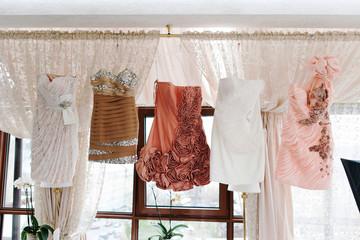 Beautiful bridesmaids dresses hanging on hangers waiting on wedding ceremony.