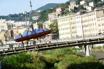 Rescue workers recover a body at the site of the collapsed Morandi Bridge in the port city of Genoa