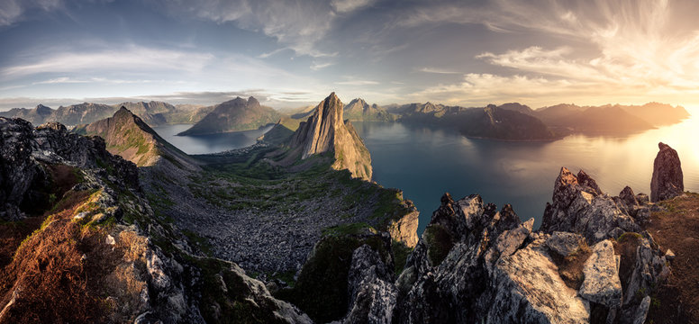Mountainous panorma landscape view with huge fjords during golden sunset in Senja, Norway