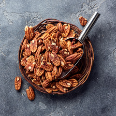 Pecan nuts and scoop on gray table