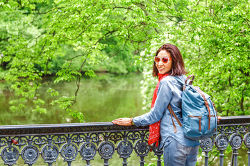 young pretty brunette woman traveling in park and standing on a bridge over old channel