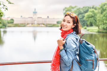 Happy female asian tourist in the baroque garden in front of the ancient architecture of royal Charlottenburg palace. Sightseeing and travel destinations in Berlin and Germany concept