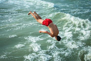 young guy falls into the water upside down