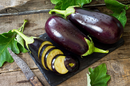 Fresh healthy raw Purple Eggplant on a kitchen wooden table. The concept of Diet menu.