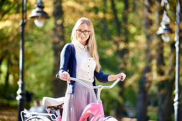 Portrait of young smiling happy attractive blond long-haired woman in glasses, skirt and blouse holding handles of pink lady bicycle on blurred colorful golden yellow green bokeh foliage background.
