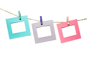 Colorful funny picture frames hanging on a rope with clothespins twine isolated on white background
