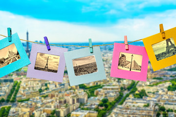 Old photos of the main attractions of Paris in a fun framework, attached with a clothes-peg clothespin to the hanging lashing rope against the backdrop of the panorama of Paris with the Eiffel Tower.