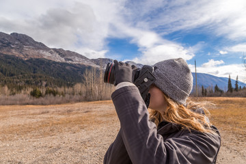 Girl taking photo of the Rocky Mountains