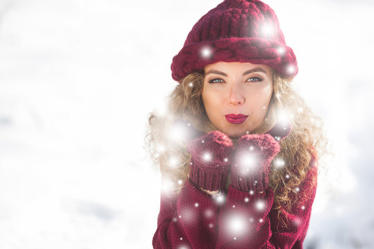 Portrait of young cheerful woman blowing snow into camera