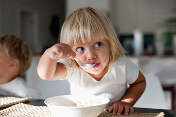 A young girl eating breakfast.