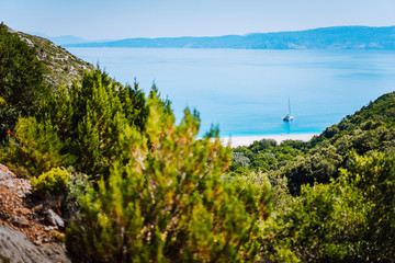 Lonely yacht on hidden Fteri beach lagoon, Kefalonia, Greece. Framed view between pine tree branches during trekking path down ravine