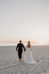 Wedding couple is going on the sea beach in sunrise.  Seaside love story. Sand, water and horizon. Love concept