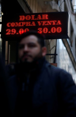 A man walks past an electronic board, which shows currency exchange rates, in Buenos Aires' financial district