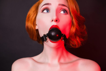 Redhead girl with gag on black background. Sexual bdsm toy. Model with open mouth. Attire for playing bdsm games. Lady with bondage on mouth. Photo in low key lighting. Black leather bondage with gag