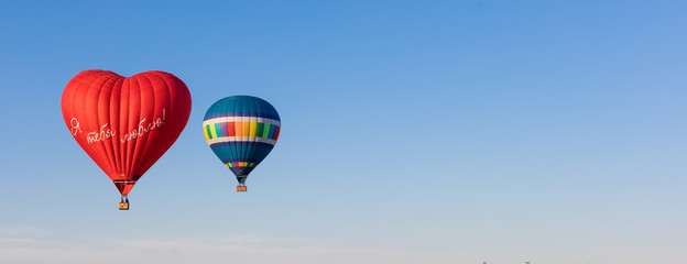 """Red heart shaped air ballon with inscription in Russian """"I love you"""" and colorful air balloons in the sky, banner"""