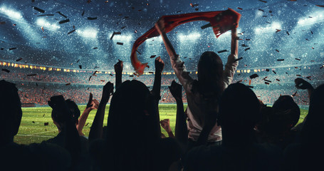 Fans celebrating the success of their favorite sports team on the stands of the professional stadium while it's snowing