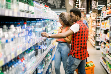 African couple shopping in beverage section at supermarket. Couple doing shopping at market while buying cold drink. Handsome guy holding shopping basket