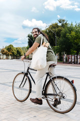 Ecological vehicle. Pleasant happy man smiling while riding bike in the city