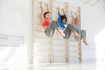Group of diverse fit women hanging with legs up on gymnastic wall bars exercising together