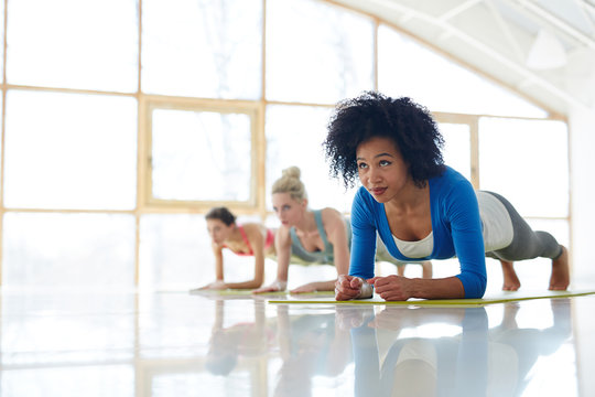 Diverse confident sportive women training abdomen with plank exercise on yoga mats in spacious white hall