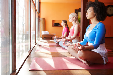 In de dag Ontspanning Side view of diverse confident women meditating together on yoga mats sitting near window in sunlight and relaxing