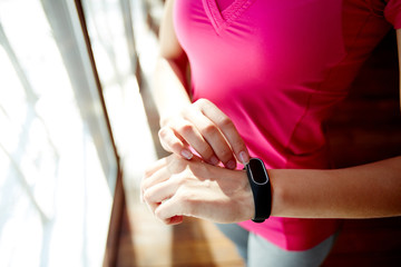 From above shot of unrecognizable woman in sportswear standing near window and using modern fitness tracker