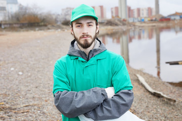 Young bearded volunteer in green uniform standing with arms crossed and looking at camera on shore