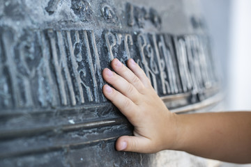 The hand of the child touches a large church bell with ancient Slavic inscriptions. The concept of spirituality. Russia. Rostov the Great.
