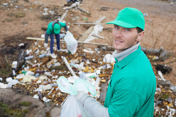 Adult volunteer with rubbish bag looking at camera and standing at litter pile