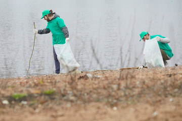Volunteers in green uniform cleaning coast and picking garbage to bags