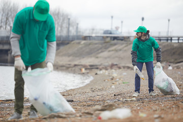 Volunteers in green uniform working and collecting garbage on shore in cloudy day
